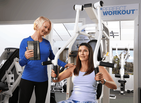 Woman working out on machine with female trainer