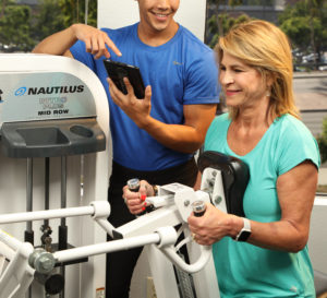 Woman working out on machine with male trainer