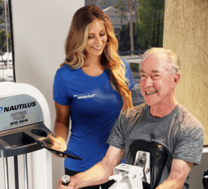 man working out on machine with female trainer
