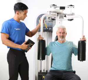 man on chest fly machine with male trainer
